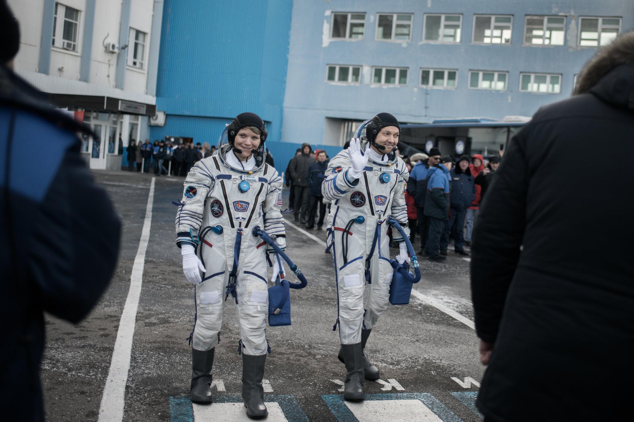 NASA'dan Anne McClain ve Soycos'un Roscosmos komutanı Oleg Kononenko fırlatma rampasına doğru giderlerken. İnsanları selamlıyorlar.