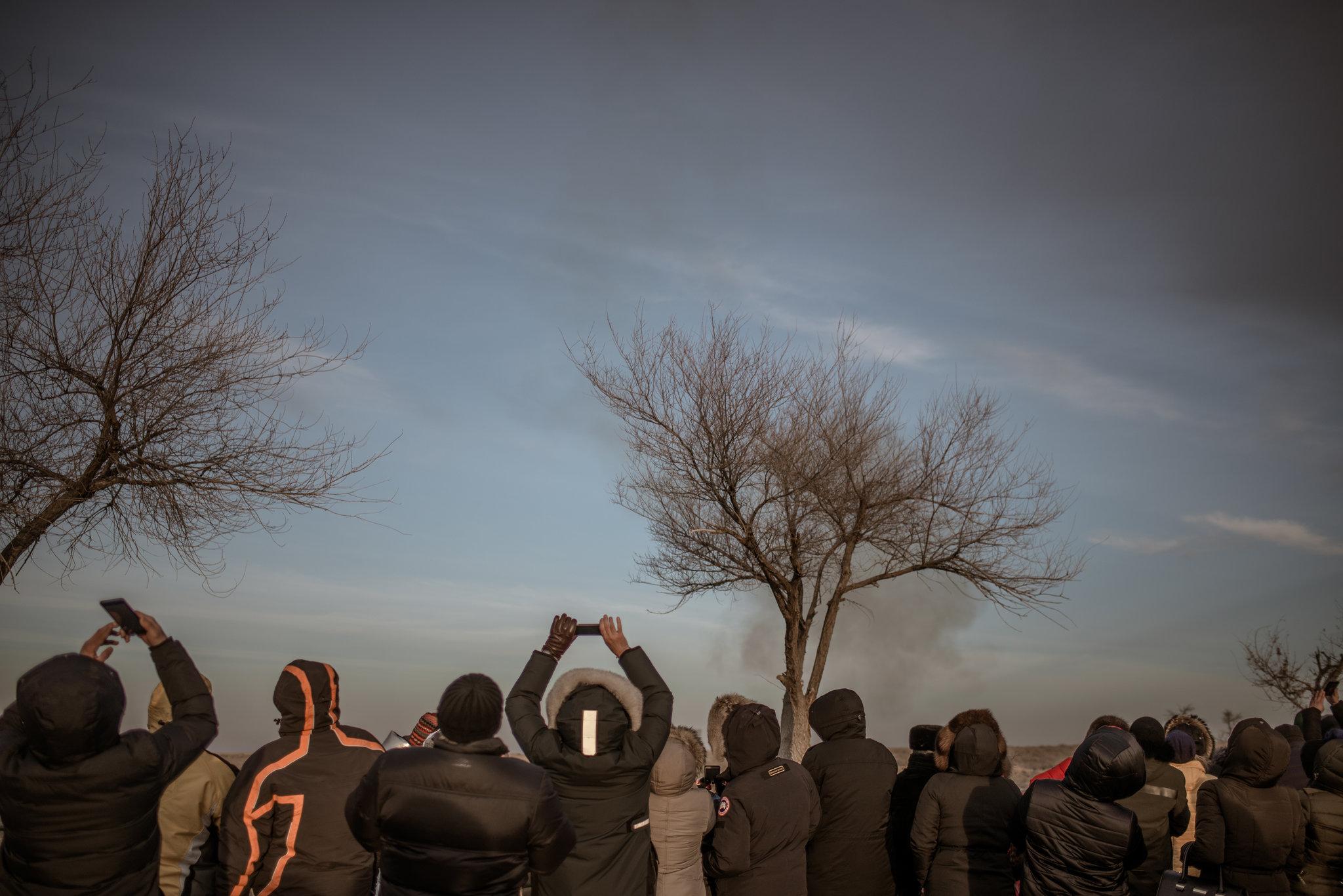 Fırlatma anını izleyen seyirciler. Ellerindeki telefonlar gökyüzüne doğrultmuşlar ve video ve fotoğraf kaydı alıyorlar.