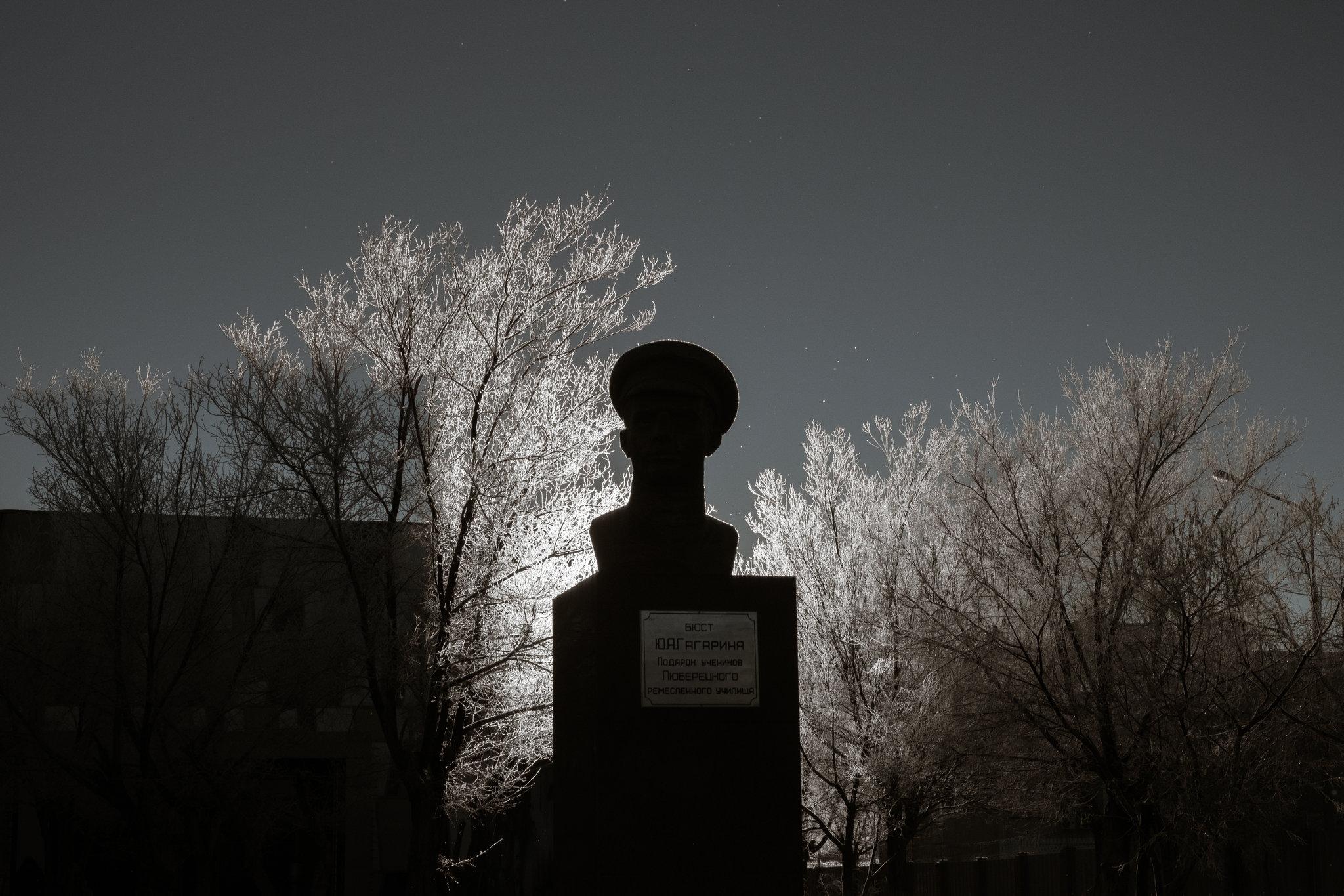 Kosmodrom müzesinin avlusunda Yuri Gagarin büstü. Işık arkadan vuruyor ve silüet görünümünde.