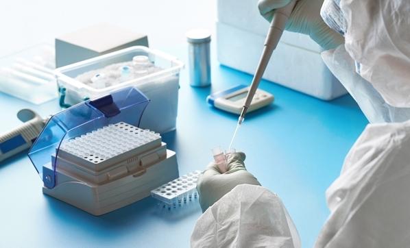 koronavirüs testi için PCR reaksiyonu hazırlayan bir araştırmacı. elinde mikropipet ve örnek içeren küçük tüp var.